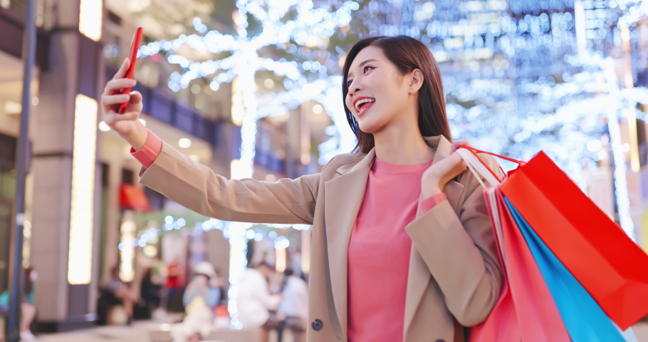 asian woman takes selfie by smart phone with some bags on her hand after shopping at night Royalty-Free Stock Footage #1064131390