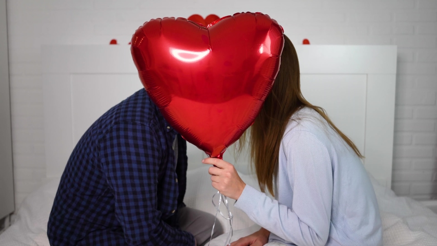 Loving couple celebrates valentine's day Man and woman with heart shaped balloon Happy smiling and kissing noses Husband and wife are flirting on bed. | Shutterstock HD Video #1064143696