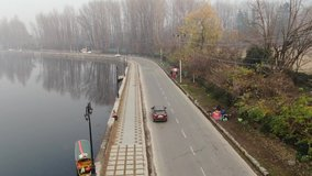 Aerial Drone Clip Of Car moving on road beside the famous dal lake kashmir india
