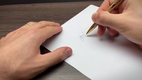 Hand signing writing yes on white paper isolated Caucasian approved verified authorized verified check gold pen brown table