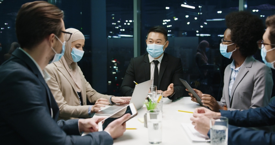 Happy multi-ethnic male and female proessionals in medical masks in modern office having team business conference working in evening and speaking about business startup, typing on laptop and tablet Royalty-Free Stock Footage #1064176765