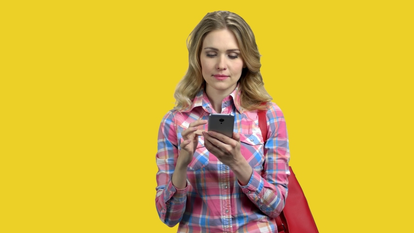Woman using cell phone on color background. Pretty caucasian girl surfing internet with phone on yellow background. People, internet, technology and communication concept. | Shutterstock HD Video #1064181586