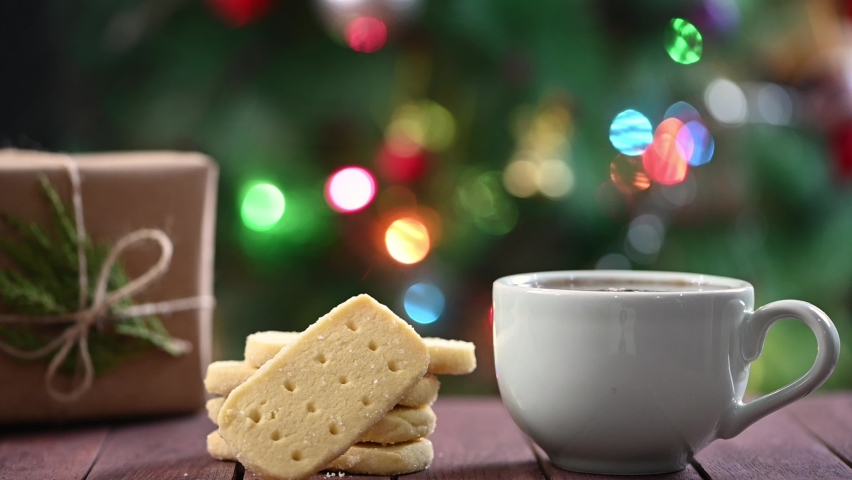 Making instant coffee. Scottish shortbread cookies and wrapped Christmas gift on table. Christmas tree at background. Royalty-Free Stock Footage #1064184814