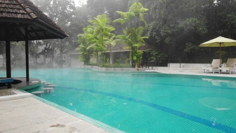 A heated swimming pool in a tropical setting in winter is damping and consuming a lot of electricity and is environmentally polluting.