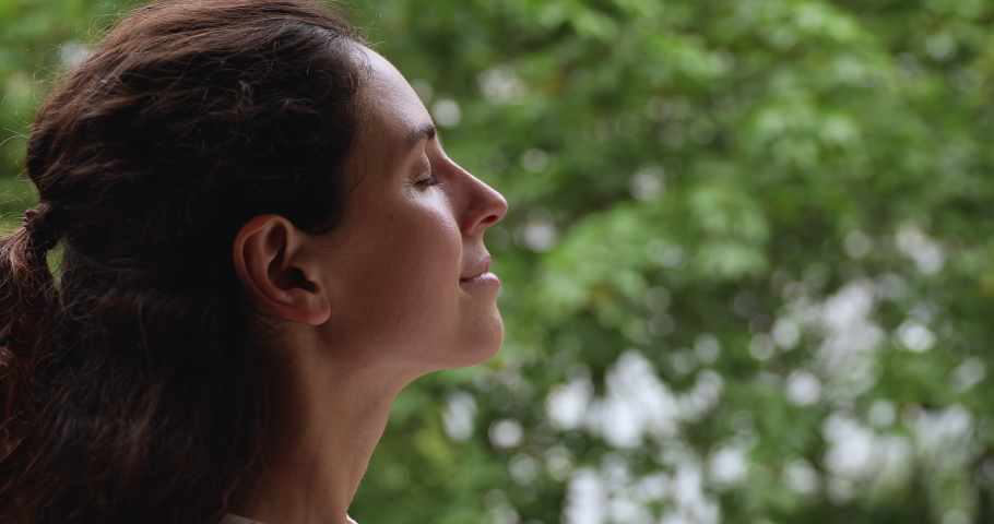 Close up head shot dreamy peaceful relaxed smiling young woman breathing fresh air, admiring nature park view, tranquil caucasian millennial lady practicing yoga exercised meditating alone outdoors.