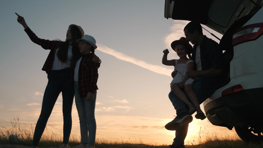 Happy family by the car at sunset. Silhouette of a family in the park. Family car trip. Silhouette of a group of happy people. Parents with children travel by car at sunset. Happy family concept