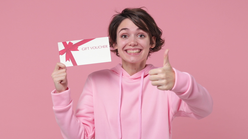 Excited brunette young woman in streetwear hoodie posing isolated on pastel pink background studio. People lifestyle concept. Pointing index finger on gift certificate showing thumb up winner gesture Royalty-Free Stock Footage #1064313076