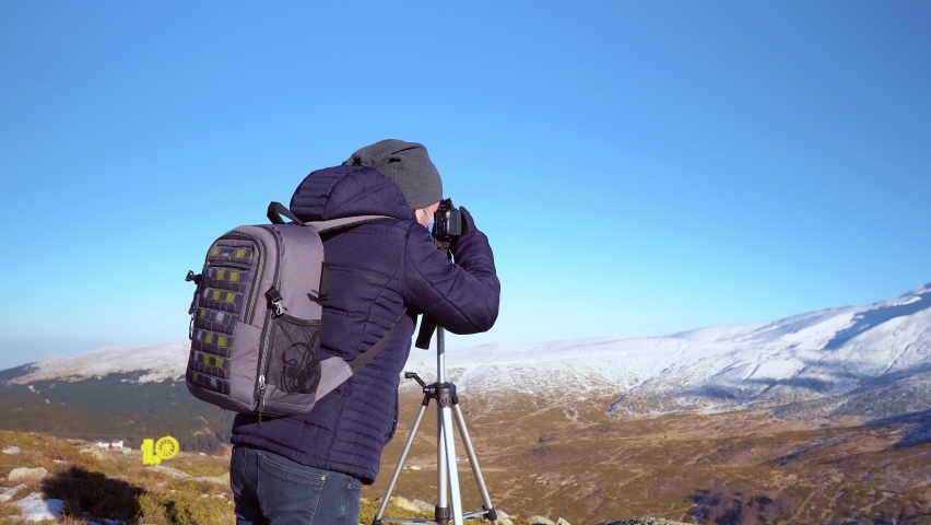 Photographer taking a picture in the cold mountains - Dolly shots | Shutterstock HD Video #1064356159