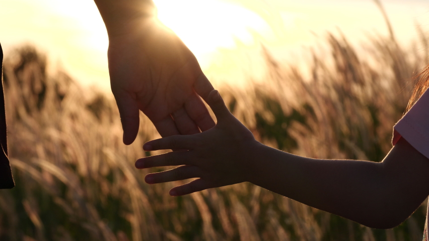 Close-up of mother and daughter hands joining together with sunset sunlight flare in natural background, Beautiful romantic moment between mother and daughter. Happy Family and Mother's Day Concept. | Shutterstock HD Video #1064359006