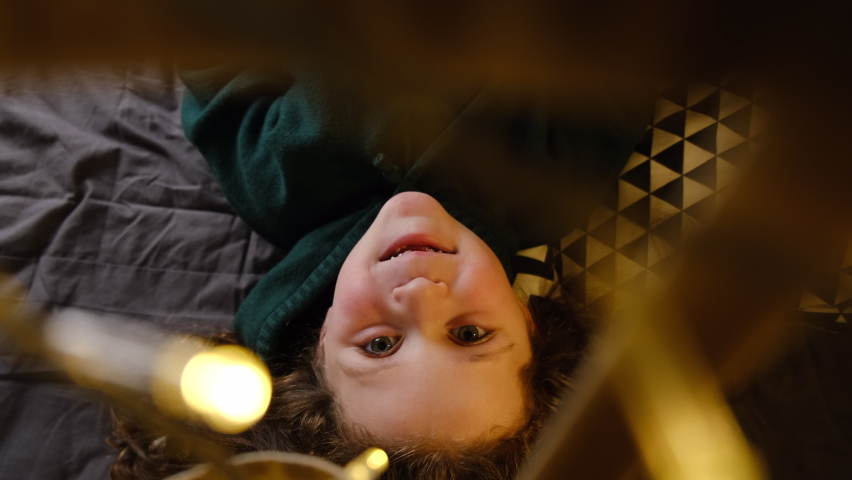 Top view of little girl vlogger blogger looking at camera talking recording vlog, preschool kid speaking to webcam making online video call having fun lying in tent decorated with festive garlands Royalty-Free Stock Footage #1064384197