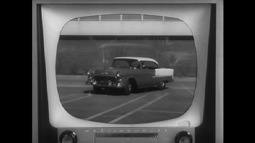 CIRCA 1950s - A man watches his wife drive on television and then arrive at their house in 1955.