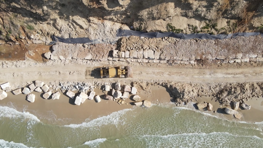 Aerial view of heavy machinery, shovel  load with rock and gravel working on the beach, bulldozer carrying rocks working on sea leavel, heavy equipment top down footage