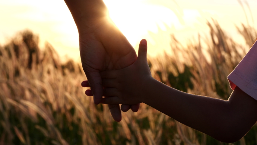 Close-up of mother and daughter hands joining together with sunset sunlight flare in natural background, Beautiful romantic moment between mother and daughter. Happy Family and Mother's Day Concept. | Shutterstock HD Video #1064447665