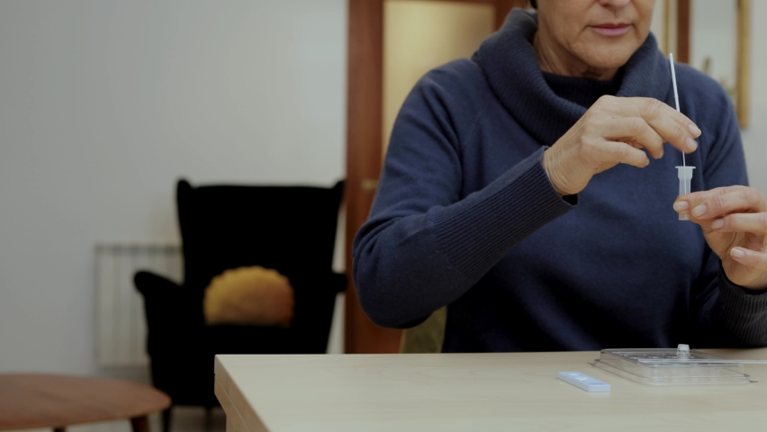 Senior woman sitting at home taking the nasal swab out of the buffer tube and closing it with a cap. Self-test Rapid antigen test for Covid-19, Coronavirus. Tracking shot Royalty-Free Stock Footage #1064483380