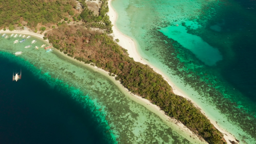 Aerial drone Island in blue lagoon with sandy beach and coral reef. Malcapuya, Philippines, Palawan. Tropical landscape with blue lagoon, coral reef | Shutterstock HD Video #1064514214