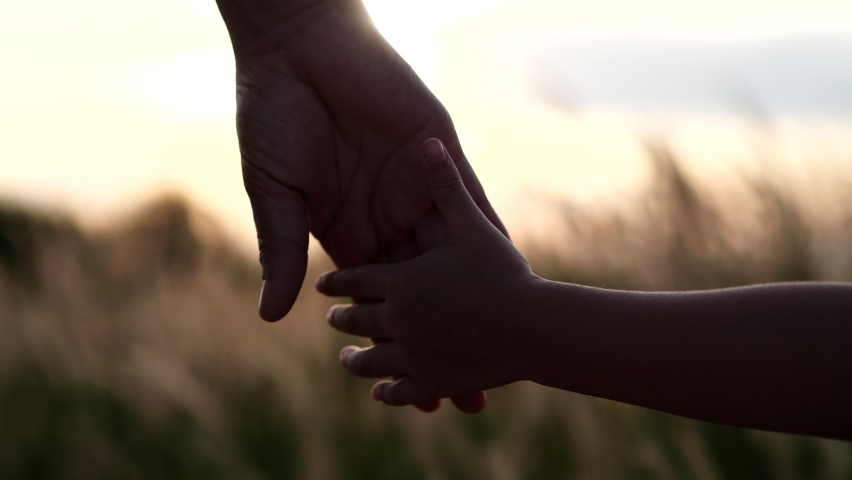 Close-up of mother and daughter hands joining together with sunset sunlight flare in natural background, Beautiful romantic moment between mother and daughter. Happy Family and Mother's Day Concept. | Shutterstock HD Video #1064529307
