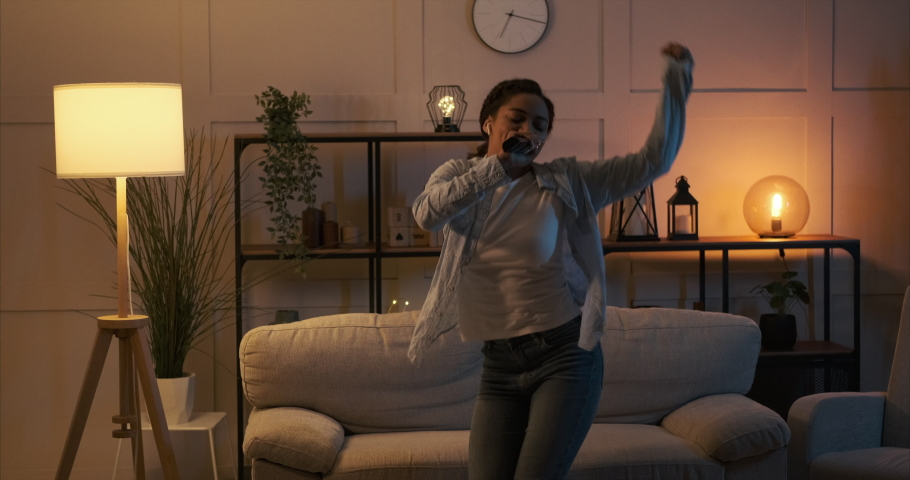 Woman singing song with remote control as mic and dancing at home | Shutterstock HD Video #1064532529