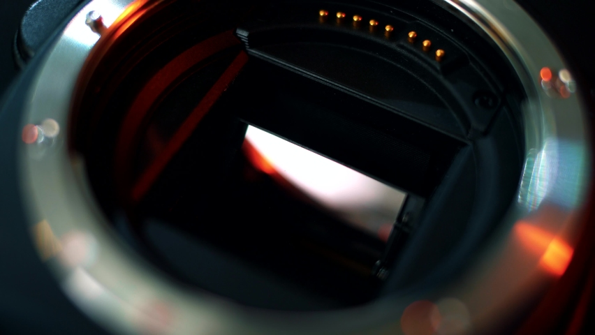 Close-up of the mirror and matrix of a professional camera. Close-up shot of the bayonet connection of a camera lens. Neon light on photo camera Royalty-Free Stock Footage #1064535163