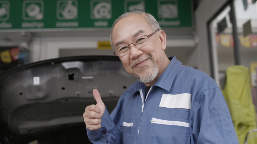 Asian elderly man are car mechanic Wear uniform, stand smiling, happy in service to customers. Professional Mechanic with factory work experience. Car maintenance business. Concept key worker Royalty-Free Stock Footage #1064549494