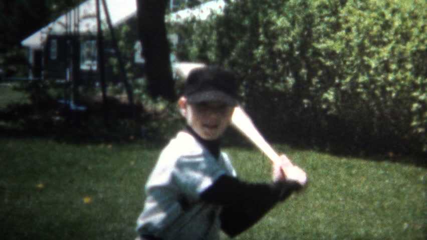 KANSAS CITY, USA - MAY 1966: Boy practice swinging like baseball legend 'Babe Ruth' by pointing to where the ball is going to go with the bat.