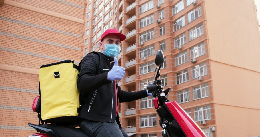 A delivery man with a yellow backpack, face mask and gloves appears in the video on an electric moped and shows a thumb up. Excellent delivery during quarantine. Royalty-Free Stock Footage #1064572384
