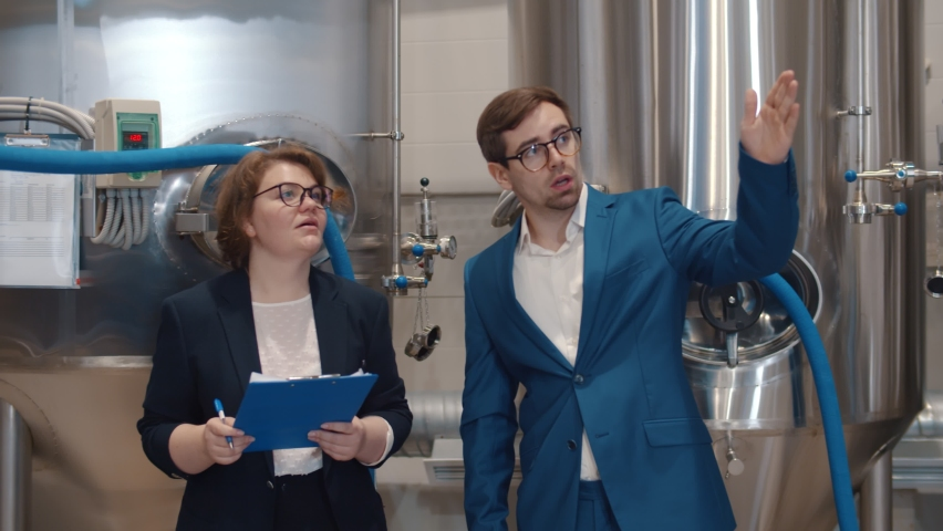 Businesswoman with clipboard listening to manager of beer factory. Female inspector in formal wear writing report doing quality control in modern brewery Royalty-Free Stock Footage #1064581357