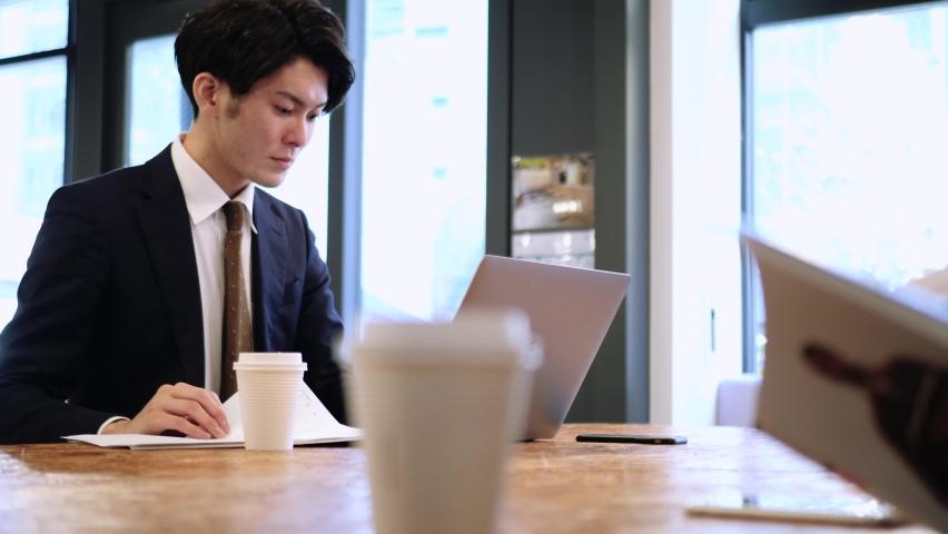 Japanese businessman man working in a shared office   Shutterstock HD Video #1064582350