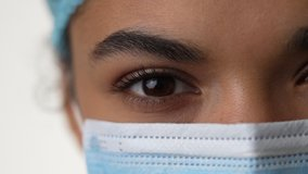 Stay safe. Close up of eyes of young female doctor wearing medical mask looking at camera isolated over white background. Healthcare and medicine concept. Selective focus on one eye. Slow motion