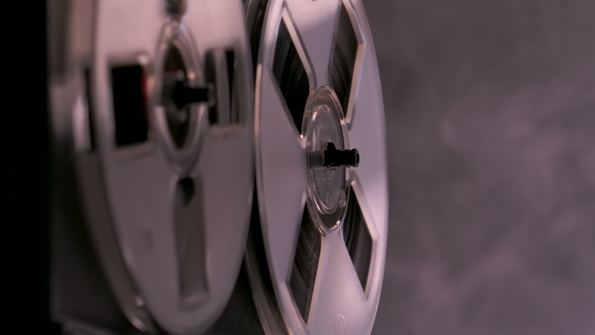 Audio reel to reel tape recorder, analog audio storage device. Tape deck plays music on dark background smoky studio with backlight. Monochrome. Spinning reels transparent close up. Slow motion. | Shutterstock HD Video #1064681251