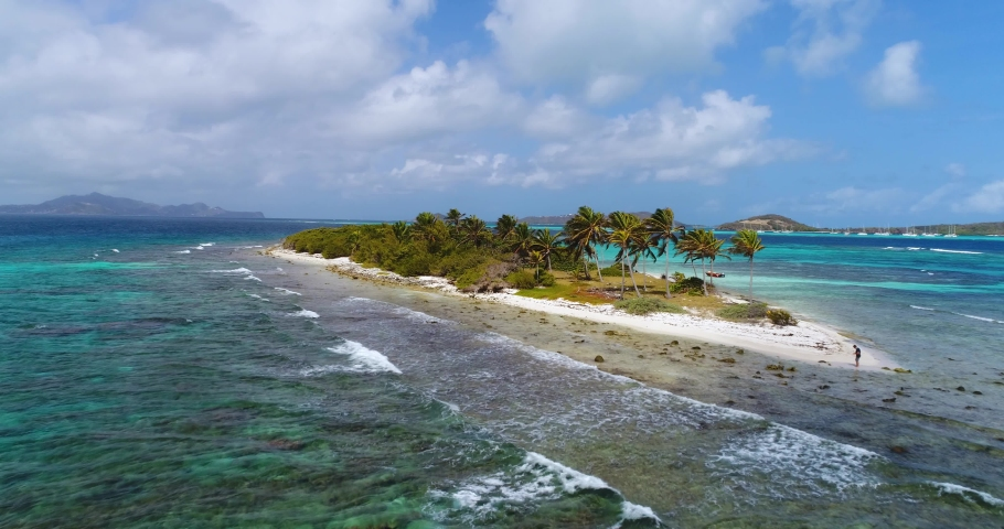 Aerial Drone Shot of a Desert Island in the Caribbean, Dream Vacation, Petit Tabac, Uninhabited Island, Saint Vincent and the Grenadines, Where they filmed Pirates of the Caribbean in the Tobago Cays Royalty-Free Stock Footage #1064684638