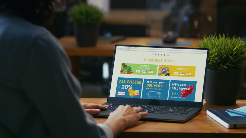 Person Uses Laptop Computer Browsing through Online Food Delivery Market, Choosing Through Vegetables Section, Fresh Goods. Internet Store Software with List of Food to Order. Over The Shoulder Royalty-Free Stock Footage #1064722507