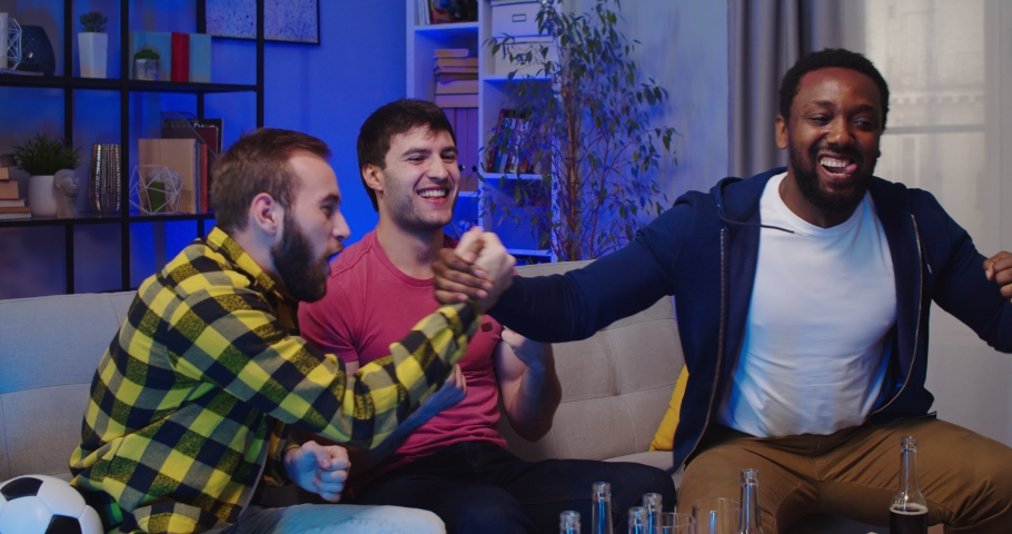 Portrait of happy joyful young multi-ethnic handsome male friends sport fans clapping their hands celebrating and watching favorite football team winning championship while sitting on sofa in evening | Shutterstock HD Video #1064741839