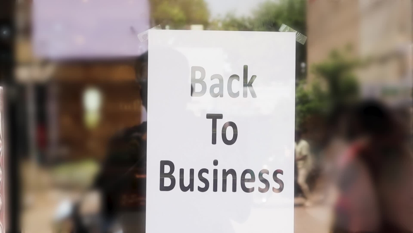Back to business poster or signage in front of store door - concept of reopening business after coronavirus or covid-19 pandemic lockdown crisis Royalty-Free Stock Footage #1064810827
