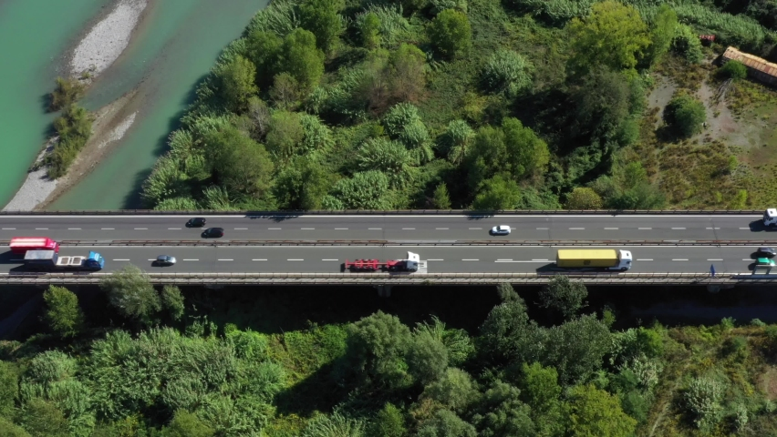 Aerial view of car traffic on the bridge that crosses the mouth of the Magra river near the village of Arcola.Bridge over the river with car traffic of trucks and cars. La Spezia, Liguria | Shutterstock HD Video #1064815954