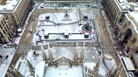 Aerial view of the snow-covered Piazza Duomo over the New Year and Christmas tree. People in the square. new year 2021. City after snowfall. Roofs of houses. Winter in Milan, Italy, December 2020: