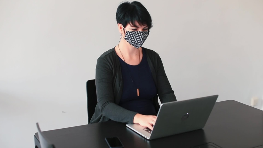 Business woman at the computer in the office wears a stylish face mask. Negotiations with partners by phone on the eve of maternity leave. A pregnant brunette is touching her belly, makes a call. Royalty-Free Stock Footage #1064835685