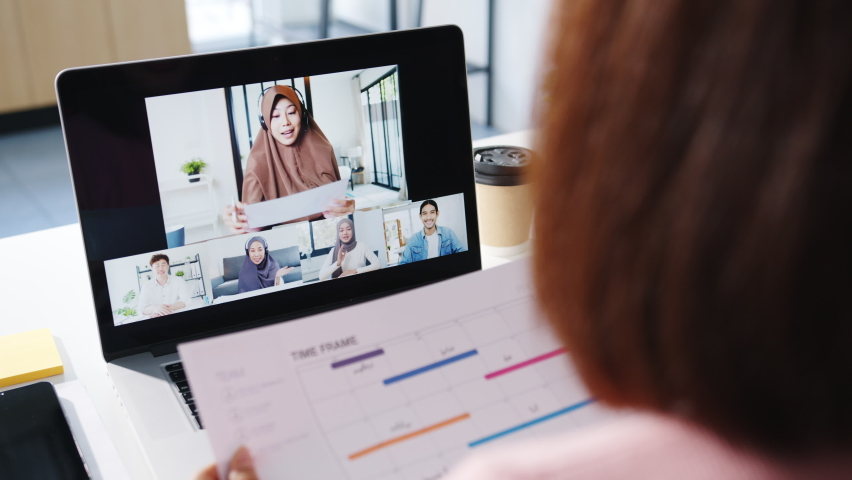 Young Asia businesswoman using laptop talk to colleague about plan in video call meeting while work from home at living room. Self-isolation, social distancing, quarantine for corona virus prevention. Royalty-Free Stock Footage #1064856772