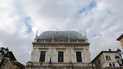 Comune di Brescia - City or town hall of Brescia, Lombardy, Italy. Round roof of an Italian building with white walls, windows, sculptures, Flags of EU and Italy. Architecture. Heritage.