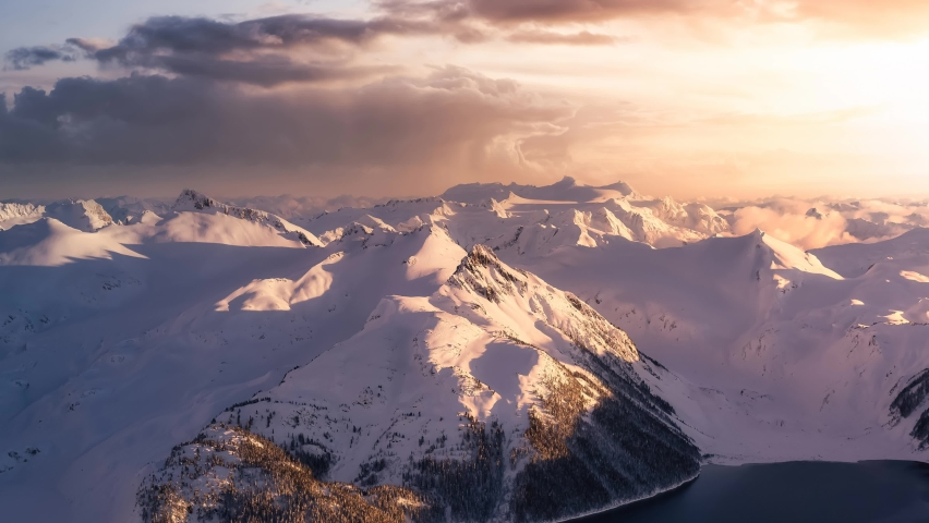 Cinemagraph Continuous Loop Animation. Aerial landscape view of the snow covered mountain range Near Whistler and Squamish, British Columbia, Canada. Garibaldi Lake. Artistic Dark Render Royalty-Free Stock Footage #1064986180