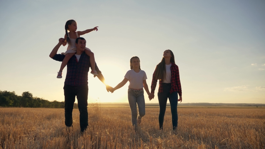 Cute happy family walks park in evening at sunset.Parents, children,dads,mother,daughter walk holding hands across field.Young happy family enjoy socializing together in park.Children, loving parents. | Shutterstock HD Video #1065024883