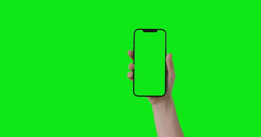 IPhone 12 Pro Max isolated on chroma key. Woman hand hold phone with a green screen in a vertical orientation portrait mode. Mockup for compositing. 2021 - USA, NY