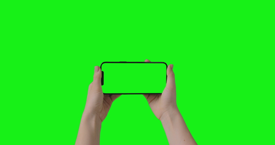 IPhone 12 Pro Max isolated on chroma key. Woman hands hold phone with a green screen in a horizontal orientation landscape mode. Mockup for compositing. 2021 - USA, NY