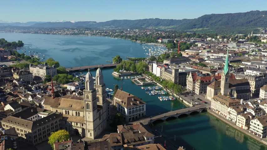 Aerial drone footage of the famous Zurich old town along the Limmat river and lake Zurich on a sunny summer day in Switzerland largest city.