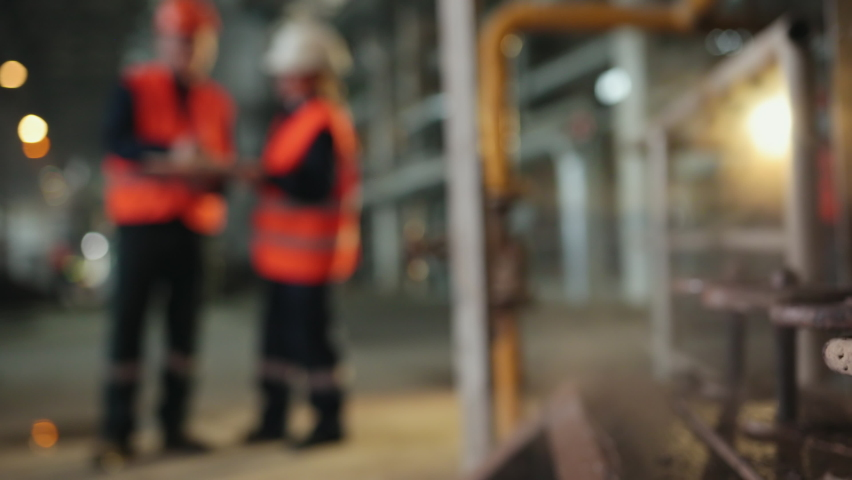 Steam taps, blurry background. Two workers at industrial plant, working together manufacturing activities. Heavy industry engineers in steel factory, discuss work. Specialist talks female technician. Royalty-Free Stock Footage #1065073774