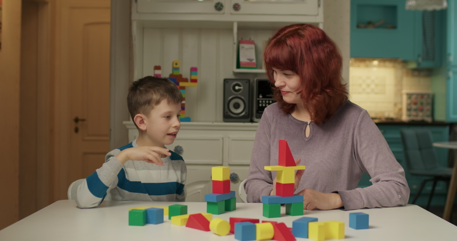 Autism psychologist working with child with autism with color wooden blocks. School boy with autism learning with mother at home. Kid building with wood blocks. Autism education. Royalty-Free Stock Footage #1065109828
