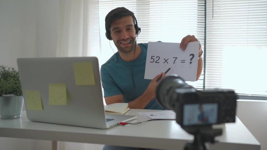 The tutor teaches students mathematics via video call with laptop computers during quarantine to prevent the covid-19 virus outbreak. Royalty-Free Stock Footage #1065113011