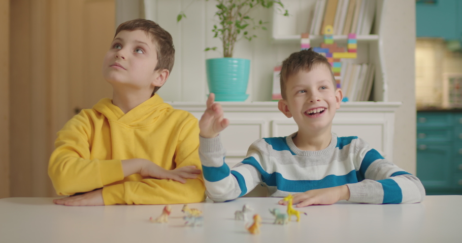 Two boys with autism playing with animals toys sitting at the table. Autistic kids learning and playing. Smiling children. Royalty-Free Stock Footage #1065123328