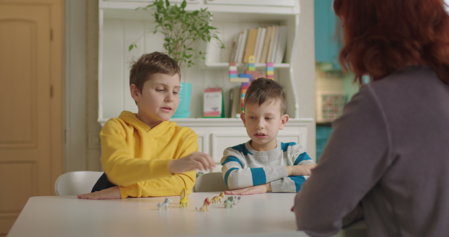 Autism therapist teaching children with autism. Two school boys with autism learning animals with tutor. Autism spectrum disorder education at home. Royalty-Free Stock Footage #1065123358