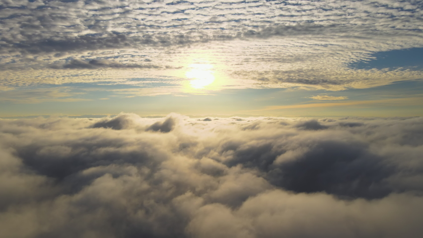 Aerial view of vibrant yellow sunrise over white dense clouds with blue sky overhead.   Shutterstock HD Video #1065158974