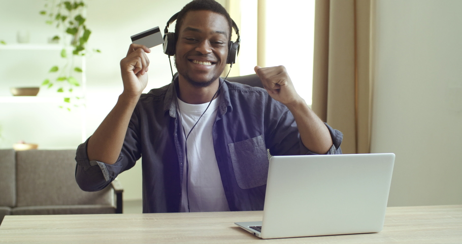 Portrait happy guy afro american business man or student sitting at table in office room at home listening to music wears headphones looks into laptop screen making purchase online using credit card | Shutterstock HD Video #1065195394